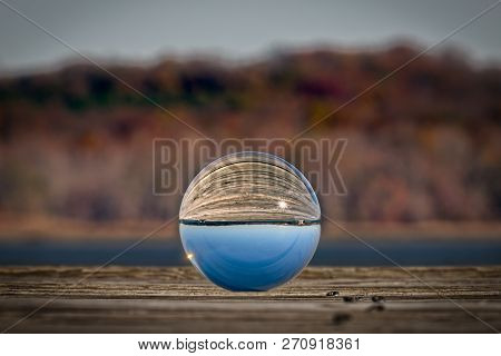 A Glass Photo Ball Sitting On A Wooden Dock In Virginia Reflecting The Morning Sun.