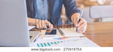 The Hand Of A Businesswoman Is Writing On A Notepad With A Pen And Using A Mobile Phone In The Offic