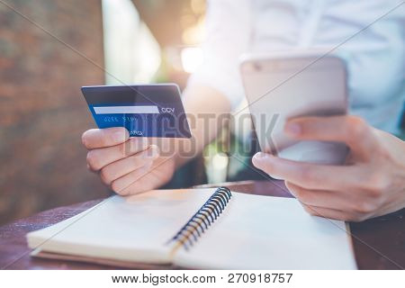 Business Woman Hand Holds A Blue Credit Card And Use Mobile Phones.