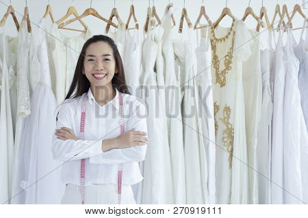 Asian Female Smilling Of Bridal Store Owner Standing With Her Arms Crossed And Smiling. Woman Tailor