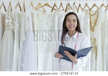 Asian Female Smilling Of Bridal Store Owner With A Diary. Wedding Dress Designer Working In Her Bout