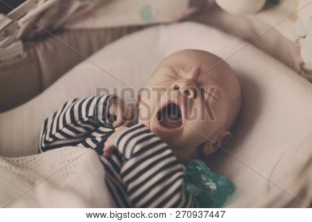 Yawning Newborn Baby Is Laying In The Bed