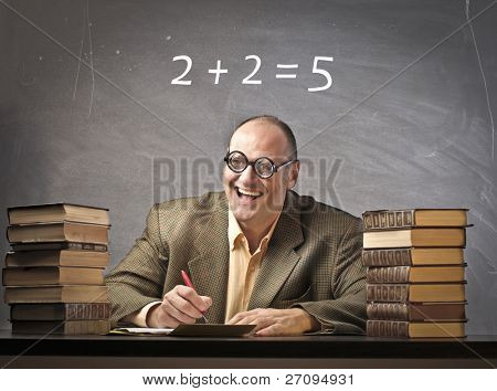 Smiling teacher in a classroom with wrong calculation on the blackboard in the background