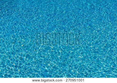 Blue Water In Swimming Pool Background. Ripple Water In Swimming Pool With Sun Reflection. Blue Swim