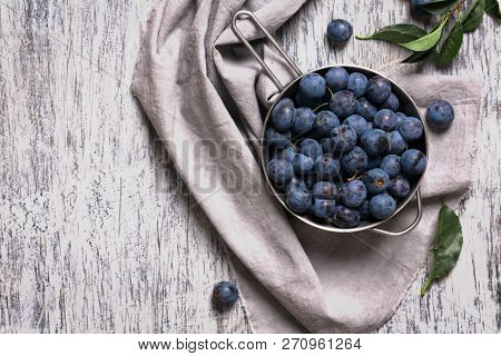 Blue Blackthorn Berries In Metallic Bowl On A Table. Gray Rustic Background