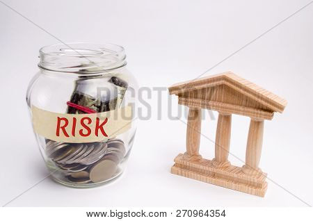 A Glass Jar And The Inscription Risk Stands Next To A State Building. The Concept Of Financial And E