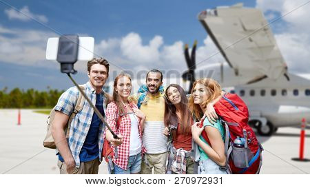travel, tourism and people concept - group of smiling friends or tourists with backpacks taking picture by smartphone on selfie stick over plane on airfield background