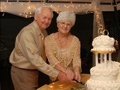 Happy Couple Celebrating Their Golden Wedding Anniversary - cutting wedding cake poster