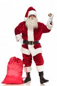 saint nick holding bell stands with hand on hip near presents bag on white background, full body picture poster