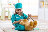 Smiling child girl playing with teddy bear and pretending she is a doctor in hospital poster