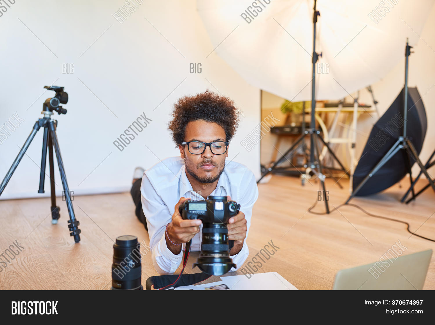 Young photographer in the photo studio or photo school inspects digital camera