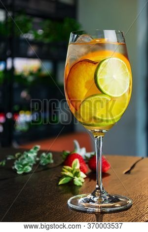 White Wine Cocktail With Slices Of Peach Lime And Orange