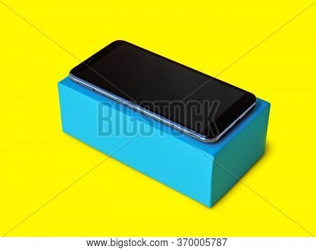 Blue Cardboard Box With A Smartphone On Yellow Background For Mockup,  Rectangular Box Mockup For Sm