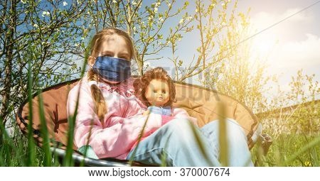 Schoolgirl With Plait In Mask Sits With Doll In Armchair Among Apple Trees Close Low Angle Shot Thro