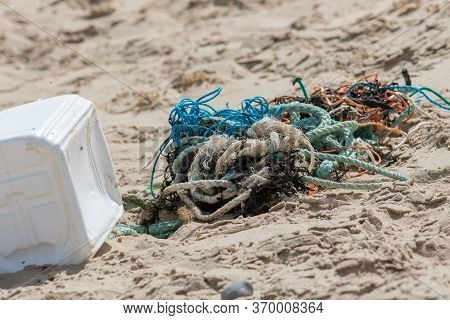 Plastic And Commercial Fishing Rope And Net Pollution On A Beach In Norfolk Uk. Fishing Net And Line