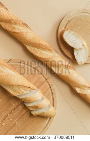 French Baguettes Are On The Table. The Baguette Is Cut Into Pieces On The Cutting Board.
