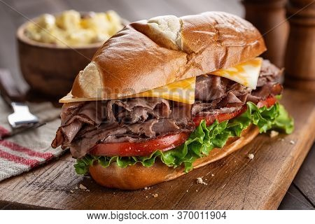 Roast Beef Submarine Sandwich With Cheese, Tomato And Lettuce On A Wooden Cutting Board