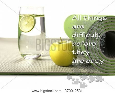 Green Yoga Mat With Apple And Glass Of Water With Lemon On White Background. Fitness Motivation Quot