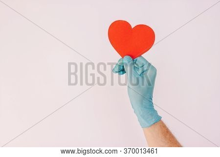 Closeup Man Doctor In Medical Latex Glove Hold Red Heart Sign In Hand Isolated On White Background.