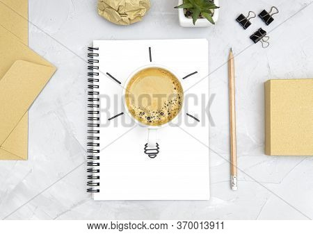 Light Bulb Symbol Made Of A Fresh Cup Of Coffee And A Sketch On A Spiral Notebook. Office Workplace