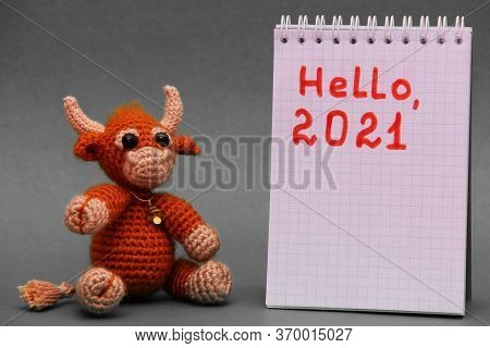 The Symbol Of The New Year 2021. The Toy Bull. Happy New Year. A Knitted Brown Toy Bull Next To A Bl