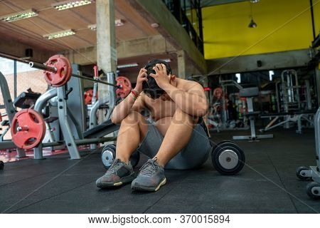 Fat Men Are Worried,fat Man Sitting On Floor After Workout In The Gym.
