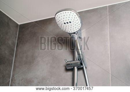 New Head Shower In A Modern Bathroom, Closeup. Shower Head On Grey Modern Wall. Bathroom Shower.