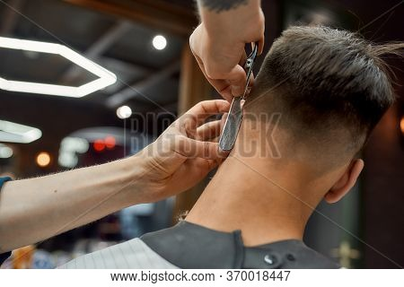 Barber Holding Straight Razor And Making Modern Haircut For His Client While Working In Barber Shop.