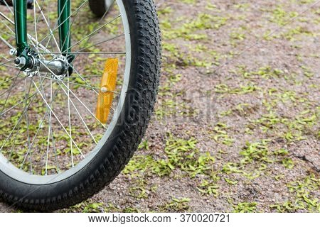 Fragment Of A Bicycle Wheel With A Plastic Orange Reflector On Metal Spokes. Traffic Safety.