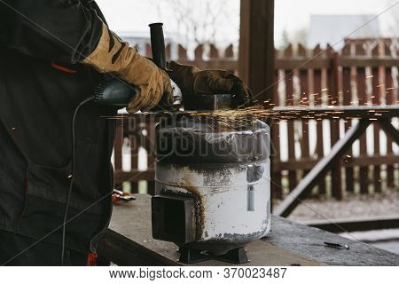 A Man In A Home Workshop Is Engaged In Reworking A Metal Product Outdoor. Circular Economy Concept.