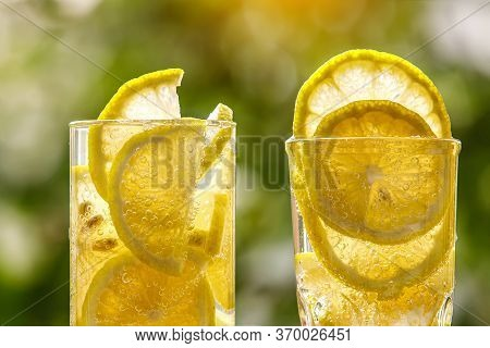 Glass Of Lemon Water On The Sunny Garden Background. Close-up View.
