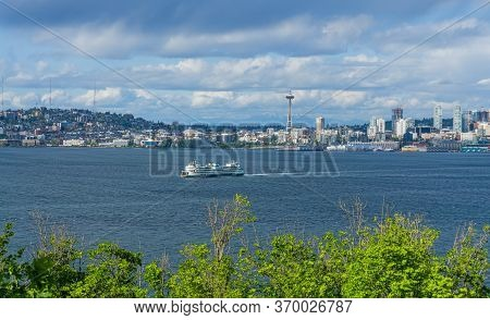 A View Of A Grassy Hill And The Seattle Skyline From West Seattle, Washington.