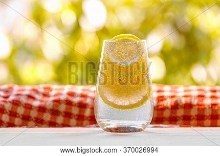 Glass Of Lemonade With Lemon On Sunny Garden Background.