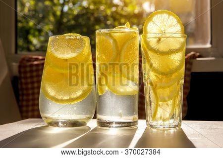 Glasses Of Lemonade With Lemon On The Sunny Room Background.