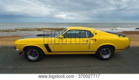 Felixstowe, Suffolk, England - May 05, 2019: Classic Yellow Ford Mustang Parked On Seafront Promenad