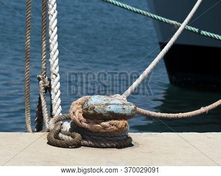 Metal Mooring Post With Knotted Ropes At Sea Harbor