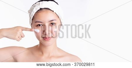 Beautiful Half Naked Asian Woman Apply Facial Cream, Lotion To Beautiful Skin On Face. Young Female