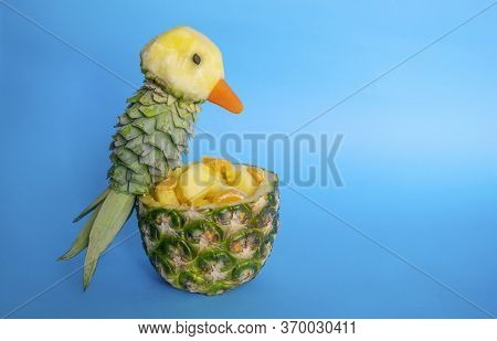 Sliced fruits In Pineapple Bowl Decorated With Parrot Carved From A Pineapple On Blue Light Backgr