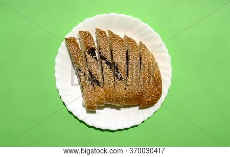 Sliced Ma'arook Bread With Date Fruit And Sesame Seeds In White Plate On Green Background, Top View.