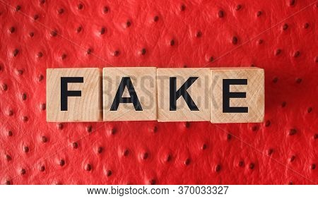 Fake Word Written In Wooden Blocks On Red Leather. Fake Or Real News, Myth Or True Concept