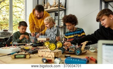 Young Technicians Building A Robot, Working With A Wiring Kit Together With A Male Teacher At A Stem