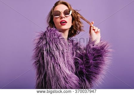 Elegant Pale Girl Wih Bright Pink Lips Plays With Short Curly Hair. Romantic Woman In Fluffy Purple