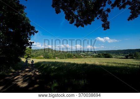 Riparbella, Italy - May 24, 2020: Unknown Women During A Trek Between Wheat Fields And Hills, In The