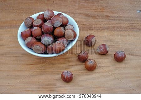 Plateful Of Hazelnuts Nuts And Spilled Hazelnuts On Wooden Background