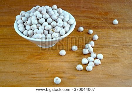 Plateful Of Organic White Chickpeas And Spilled White Chickpeas On Wooden Background