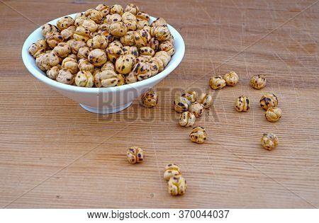 Plateful Of Organic Roasted Spicy Chickpeas And Spilled Chickpeas On Wooden Background