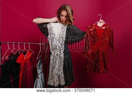 Unsure Young Female Model Holding Hangers With Two Dresses, Preparing For Party. Pensive Dark-haired