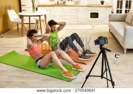 Young Couple Recording Video Blog Or Vlog About Healthy Lifestyle On Camera While Exercising At Home