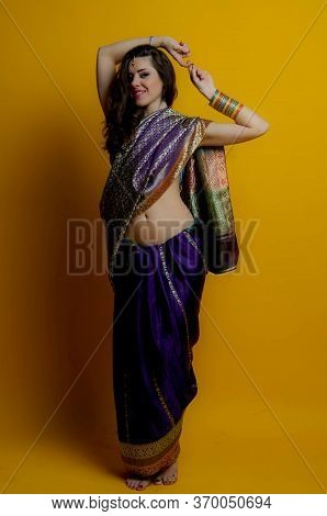The Young Dark-haired Woman In A Beautiful Indian Sari Stands Barefoot, Clasped His Hands Above The