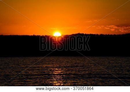 Bright Sunset Over The Lake. The Orange Sun Sets Over The Forest. Yellow Sunset. Dark Water.